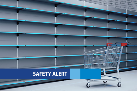 A shopping trolley in front of empty supermarket shelving