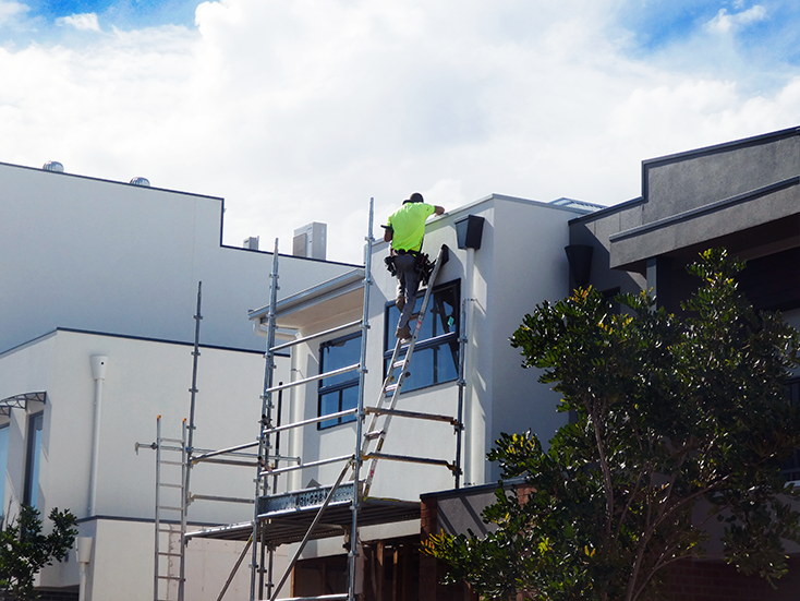 Worker standing on top of a ladder which is set up on a scaffold. No fall protection is in place.