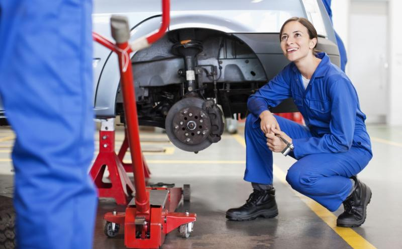 Female mechanic next to wheel bracket