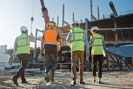 A group of people walking up to a construction site.