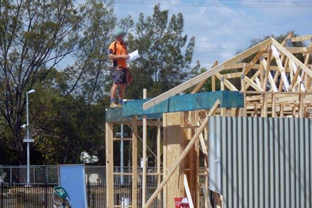 Person standing on the top plate of a roof without any fall protection.