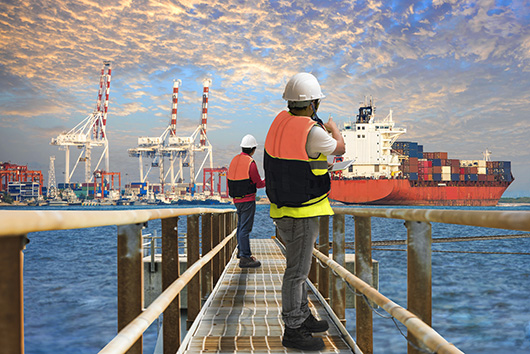 Two workers looking at cargo ship