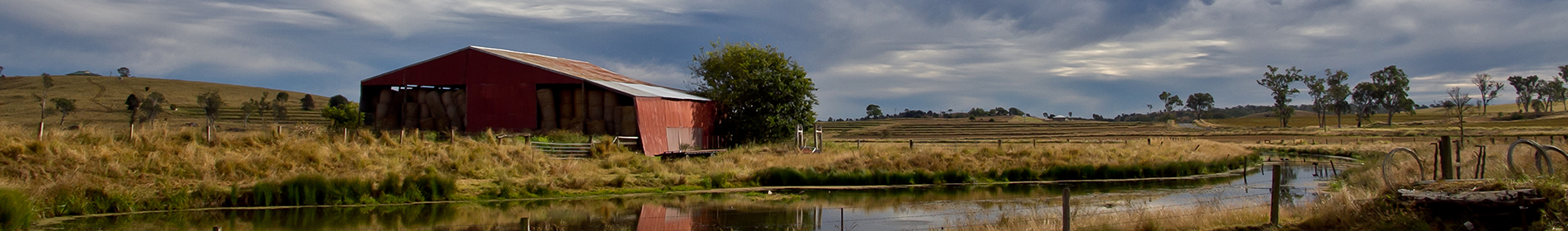 Panarama image of a farm shed and dam